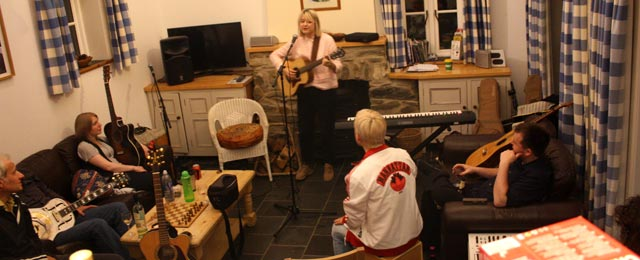 Catherine Rudie plays a song for the other songwriters in the living room of the cottage.
